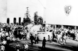 Strikers attack a studio policeman's car trying to break through the picket line at Warner Brothers Studio.